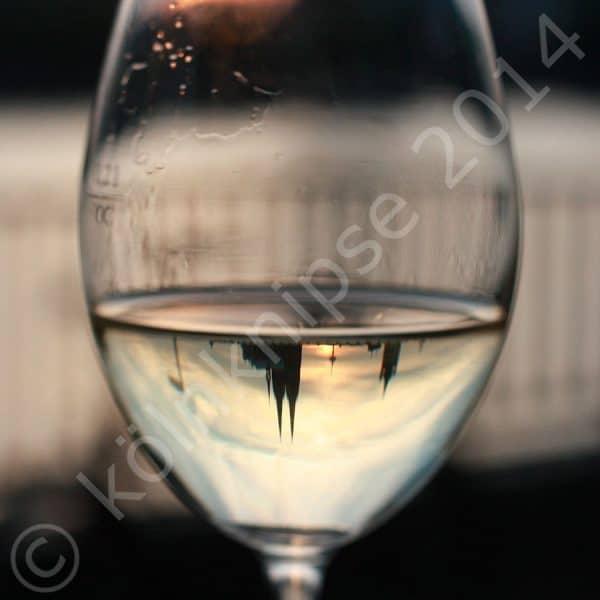 Weinglas mit Spiegelung Kölner Dom auf dem Kopf