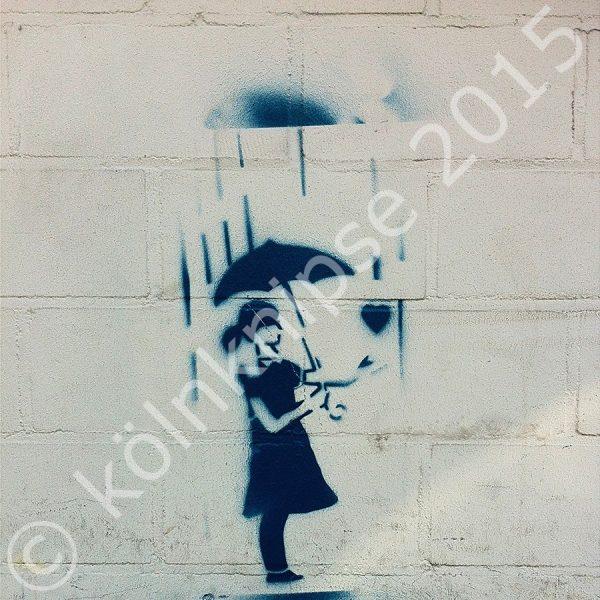 Blaues Graffiti auf weißer Fassade: eine Frau steht unter einem Regenschirm und streckt einem Herz ihre Hand entgegen