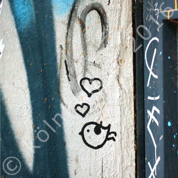 Fassade mit einem gemalten kleinen, dicken Vogel und Herzen